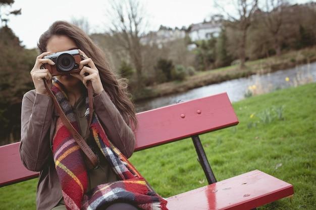 Frau, die foto von der digitalkamera nimmt