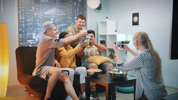 Frau, die foto von freunden macht, die auf sofa mit cocktails durch smartphone sitzen