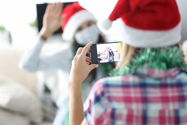 Frau, die foto von ihrem freund im weihnachtsmannhut macht