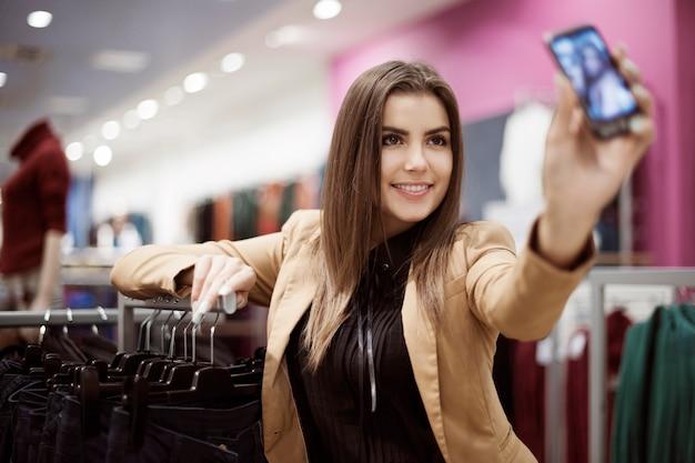 Frau, die foto von sich im einkaufszentrum nimmt