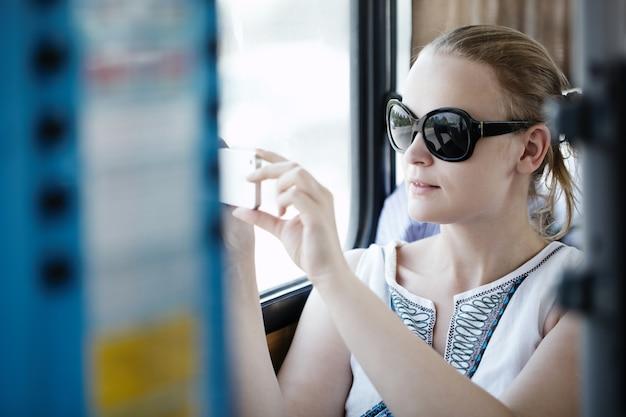 Frau, die fotos an ihrem mobile auf einem bus macht