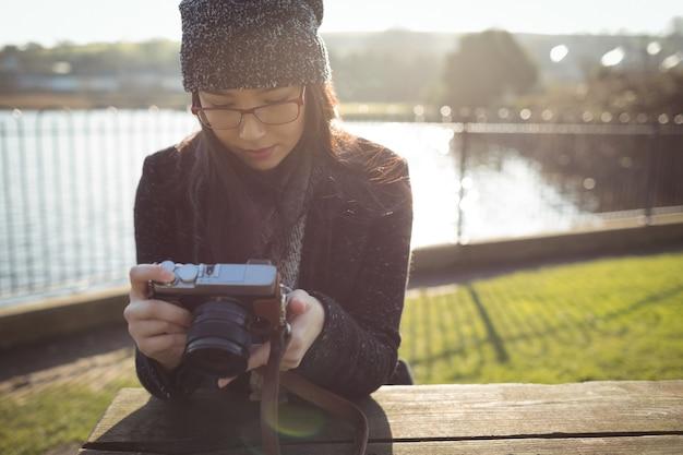 Frau, die fotos auf digitalkamera betrachtet