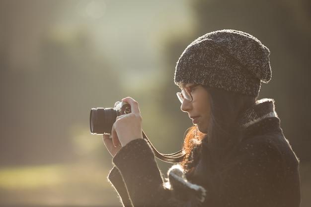 Frau, die fotos auf digitalkamera im park nimmt