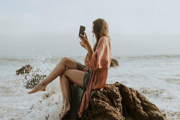 Frau, die fotos mit ihrem telefon auf dem strand macht