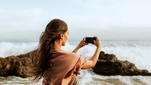 Frau, die fotos vom meer macht