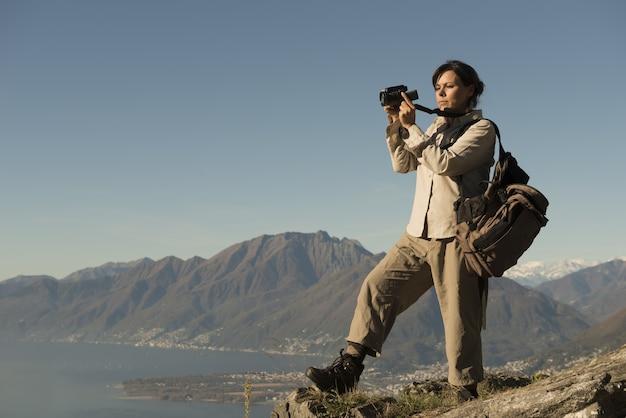 Frau, die fotos von einem berg überblickend einen see im tessin, schweiz macht