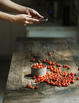 Frau, die fotos von roten kirschtomaten macht