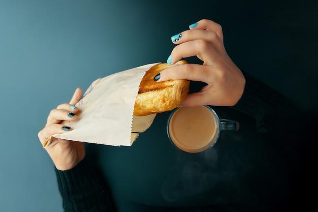 Frau, die französisches hörnchen und kaffee auf einer dunklen tabelle frühstückt