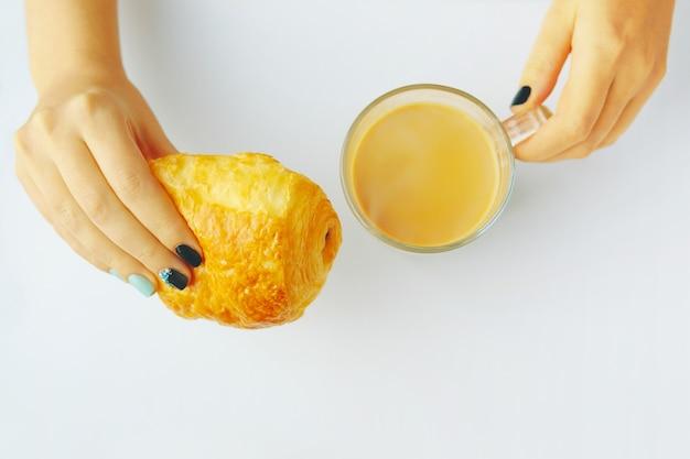 Frau, die französisches hörnchen und kaffee auf einer weißen tabelle frühstückt