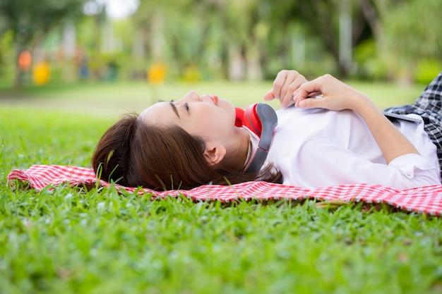 Frau, die freizeit auf tischdecke trägt und tablette verwendet, um musik draußen in einem üppigen grünen park zu hören