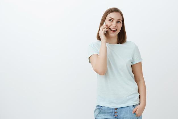 Frau, die freudig mit freund spricht, kann stundenlang am telefon hängen. gesellige glückliche und entspannte gutaussehende frau im t-shirt, jeans, die hand in der tasche und smarpthone nahe ohr hält, das mit lächeln beiseite schaut