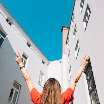 Frau, die friedensgeste nahe wohngebäude macht