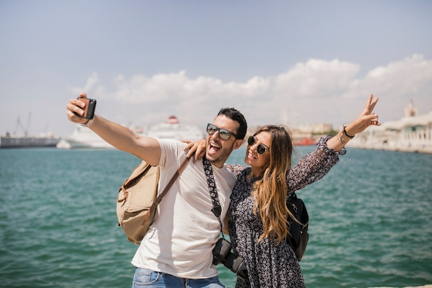 Frau, die friedenszeichen mit ihrem freund nimmt selfie auf mobile macht