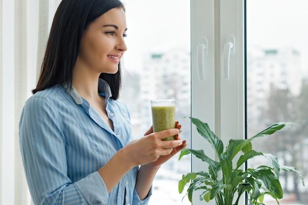 Frau, die frisch gemischten grünen kiwi smoothie trinkt