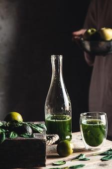 Frau, die frisch gemischten grünen und weißen smoothie im glasglas mit bestandteilen herum auf einem rustikalen holztisch gießt. gesundes essen und lebensstilkonzept. detox-diät. rezeptideen.