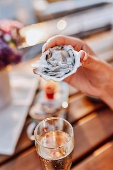 Frau, die frische austern isst und gekühlten proseccowein auf dem sommersonnenuntergang trinkt. meeresfrüchte-delikatessen