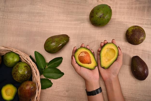 Frau, die frische avocado auf hölzernem hintergrund hält.
