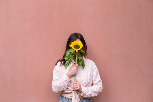 Frau, die frische gelbe blume nahe gesicht hält