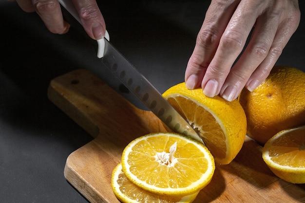Frau, die frische gesunde orangenscheiben auf holzbrett schneidet