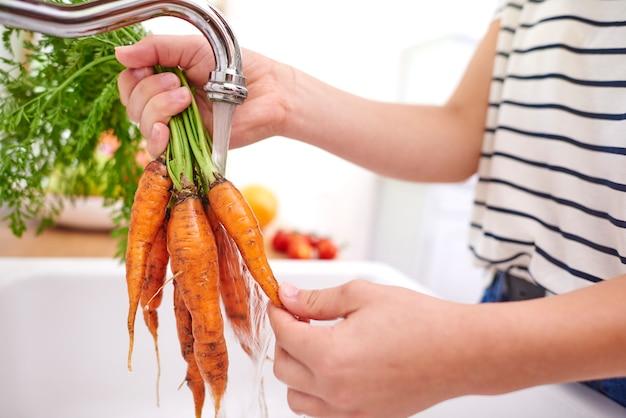 Frau, die frische und organische karotten wäscht