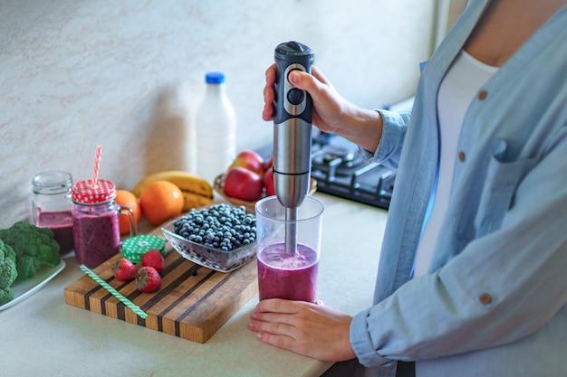 Frau, die frischen blaubeer-smoothie unter verwendung des stabmixers an der küche zu hause kocht. gesundes essen