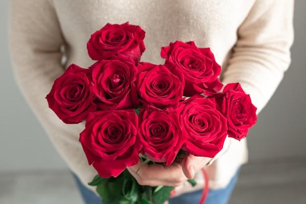 Frau, die frischen blühenden blumenstrauß der roten rosen hält