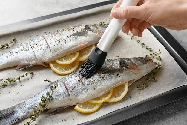 Frau, die frischen fisch gefüllt mit zitronenscheiben auf backblech zubereitet