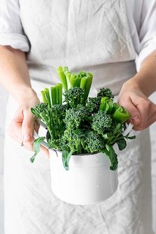 Frau, die frischen organischen brokkoli hält