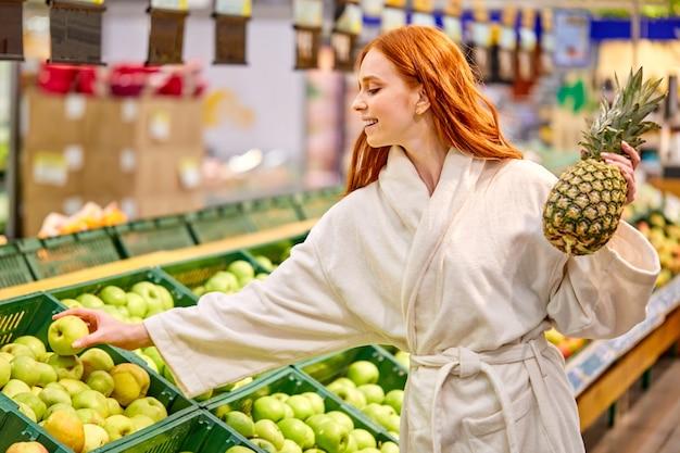 Frau, die frisches obst im lebensmittelgeschäft wählt, frau im bademantel genießt das einkaufen allein, steht im gang und hält ananas in händen