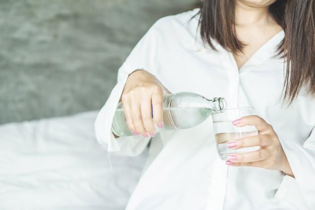 Frau, die frisches wasser im bett trinkt