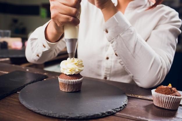 Frau, die frischkäseoberteil auf cupcakes in der küche macht. kuchen kochen.
