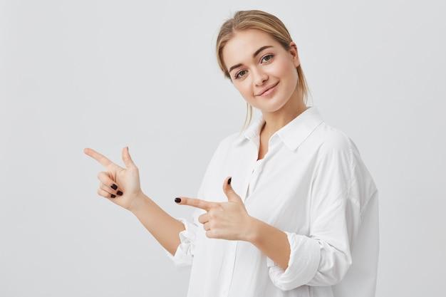 Frau, die fröhlich lächelt und ihre zeigefinger zeigt und kopienraum für ihren text oder werbeinhalt zeigt. studioaufnahme des attraktiven jungen blonden mädchens lokalisiert auf grauem hintergrund