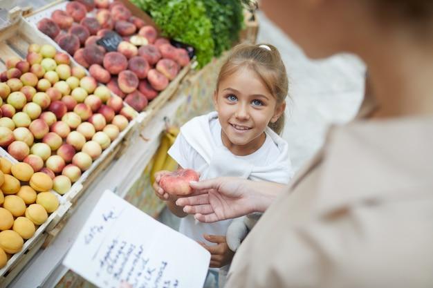 Frau, die früchte im supermarkt wählt