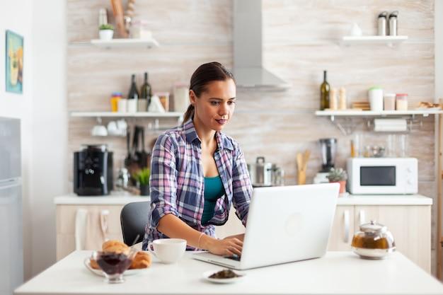Frau, die früh morgens am laptop arbeitet und eine tasse grünen tee trinkt