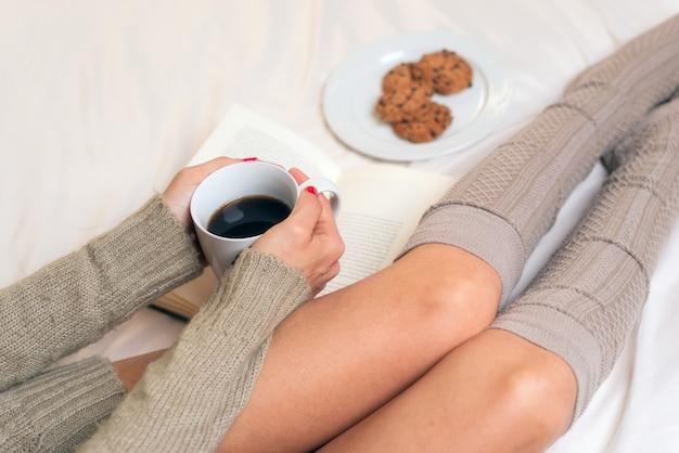 Frau, die frühstück im bett beim lesen eines buches isst