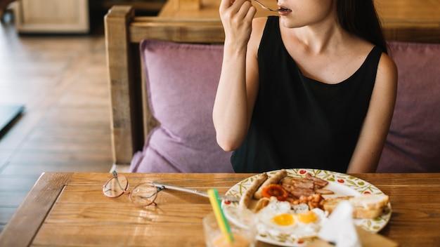 Frau, die frühstück im restaurant isst