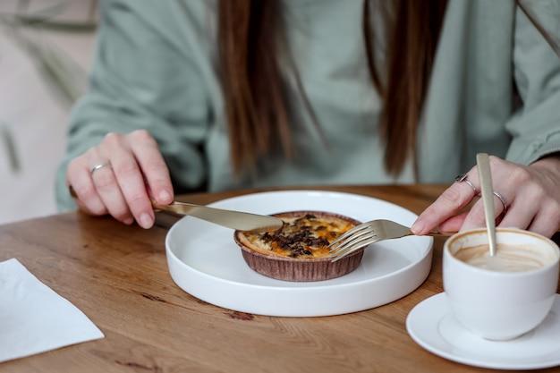 Frau, die frühstück in einem café isst. eine nicht wiederzuerkennende frau schneidet ihre pilzquiche, um sie mit einem kaffee zu essen. menschen und esskonzept.