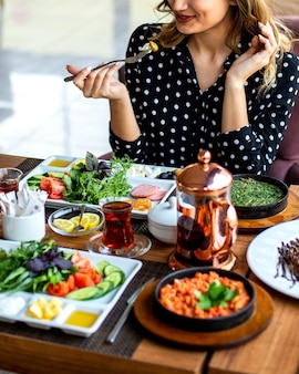 Frau, die frühstücks-rührei mit kräutergemüsekräutern und tee isst