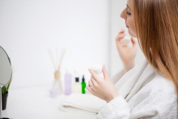 Frau, die für arbeit fertig macht, die morgenschminke im badezimmerspiegel zu hause tut.
