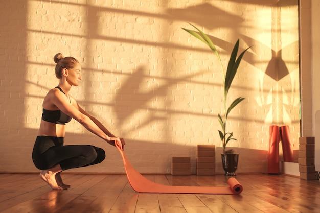 Frau, die für das handeln von yoga sich vorbereitet, eine matte auf dem boden hinlegend