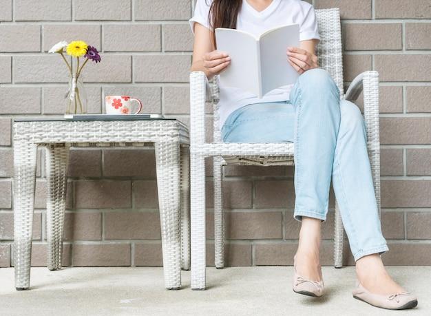 Frau, die für das lesen eines buches in der freizeit sitzt