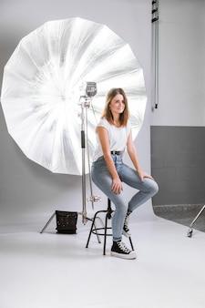 Frau, die für ein foto auf stuhl aufwirft