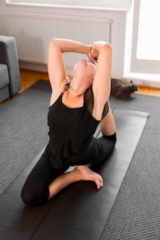 Frau, die für körperliche übungen hohe ansicht aufwärmt