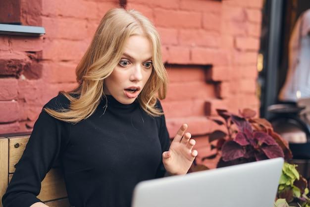 Frau, die für laptop in einem café auf der straße nahe einem freiberufler des backsteingebäudes arbeitet