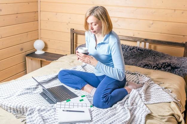 Frau, die für laptop von zu hause auf bett arbeitet. mädchen, das tragbaren computer zum schreiben auf tastatur in ihrem büro mit tasse kaffee verwendet