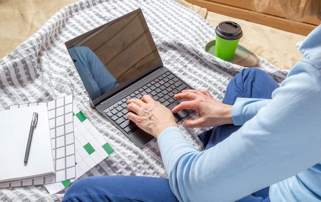 Frau, die für laptop von zu hause auf bett arbeitet.