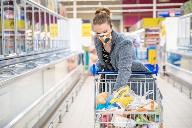 Frau, die für lebensmittel in einem supermarkt während einer coronavirus-epidemie mit einer medizinischen maske auf ihrem gesicht einkauft