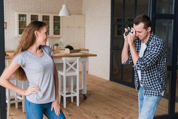 Frau, die für schuss während mann verwendet fotokamera aufwirft