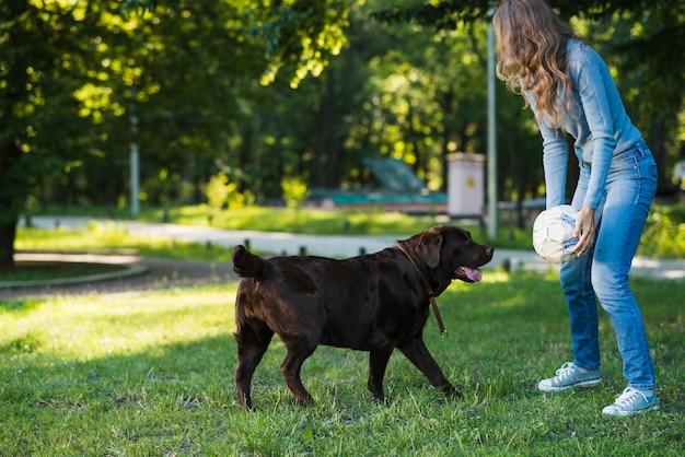 Frau, die fußball mit ihrem hund im garten spielt