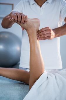 Frau, die fußmassage vom physiotherapeuten erhält